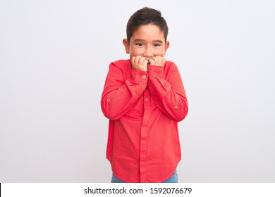 Beautiful kid boy wearing elegant red shirt standing over isolated white background looking stressed and nervous with hands on mouth biting nails. Anxiety problem.