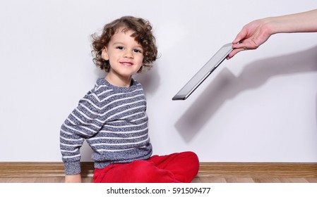 Beautiful kid playing games on a tablet. Boy sitting on the floor and looking on the display of a tablet watching cartoons. Mothers hands giving her boy a tablet and making him very happy