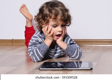 Beautiful kid playing games on a tablet. Amazed boy sitting on the floor and looking on the display of a tablet watching cartoons.