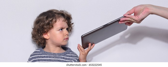 Beautiful kid playing games on a tablet. Boy sitting on the floor and looking on the display, screen of a tablet watching cartoons. Very angry kid because his mother took the tablet from him.
