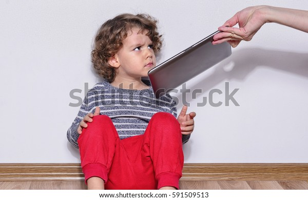 Beautiful kid playing games on a tablet. Boy sitting on the floor and looking on the display of a tablet watching cartoons. Very angry kid because his mother took the tablet from him