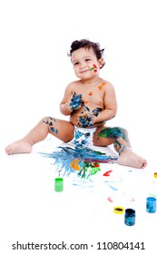 A beautiful kid playing with his paints. The inky boy is busy with his paintings. The toddler is wearing diaper.