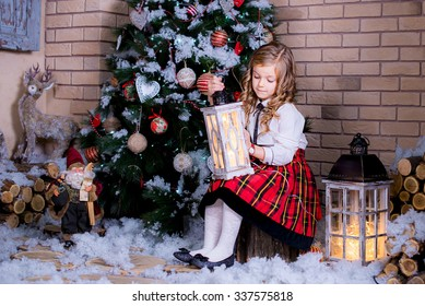Beautiful kid sitting near the Christmas tree with a flashlight in his hand