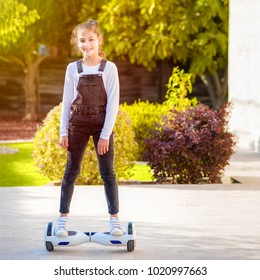 Beautiful kid Smile with Braces.Young hipster teenager girl  balancing on electric Hover Board, Dual Wheel Self Balancing Electric Skateboard at the sunny park, child using two-wheeled board.