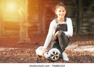 Beautiful kid Smile with Braces.Young hipster teenager girl sit with electric Hover Board,  Dual Wheel Self Balancing Electric Skateboard  at the sunny park, child using two-wheeled board. Copy space.