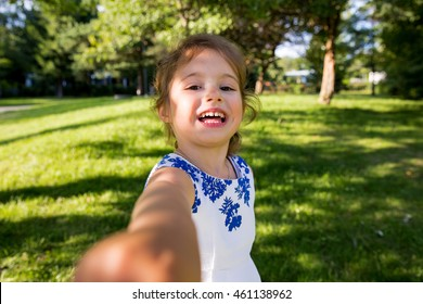 Beautiful kid taking selfie in green summer park, laughing, having fun. Warm sunny weather, healthy child, happiness, freedom, emotions. Cute girl reaching hand to camera.