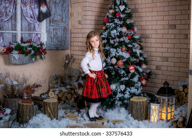 beautiful kid wearing a white shirt and a kilt standing near the Christmas tree in the snow