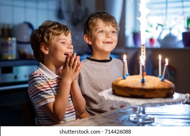 Beautiful kids, little boys celebrating birthday and blowing candles on homemade baked cake, indoor. Birthday party for siblings children. Happy twins about gifts and frirework