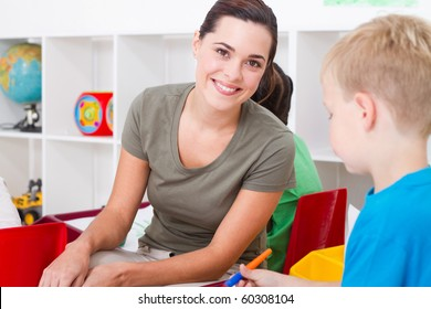 beautiful kindergarten teacher in classroom with kids