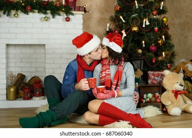 Beautiful kissing couple in love drinking tea on the background of a Christmas tree, having a rest on Christmas holidays before the new year