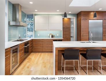 Beautiful Kitchen in Contemporary Luxury Home with Waterfall Island, Counter to Ceiling Backsplash Tile, and Elegant Hardwoods