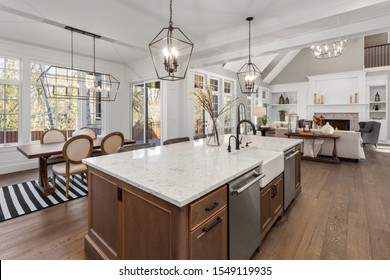 Beautiful kitchen, dining room, and living room in new traditional style luxury home. Features quartz counters, hardwood floors, and stainless steel appliances. Lights are on.