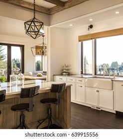 Beautiful Kitchen Interior Detail in New Luxury Home at Sunrise. Features Farmhouse Sink, Kitchen Island, Elegant Pendant Light Fixtures, and Hardwood Floor