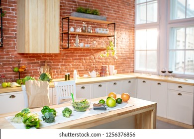 Beautiful kitchen interior with green raw food on the table