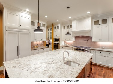 Beautiful Kitchen Interior with Island, Sink, Cabinets, and Hardwood Floors in New Luxury Home. Large island with sink provides ample room for food preparation.
