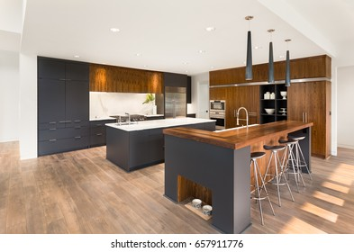 Beautiful Kitchen Interior with Island, Sink, Cabinets, and Hardwood Floors in New Luxury Home. Boasts Two Islands, Two Sinks, Stainless Steel Appliances, and Stunning Hardwood Cabinets.