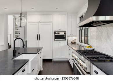 Beautiful Kitchen Interior in New Luxury Home with Dark Hardwood Floors, Two Sinks, and White Woodwork and Counters