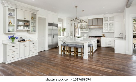 Beautiful kitchen interior in new luxury home, with white cabinets and woodwork, pendant lights, stainless steel appliances, and large kitchen island. Features stainless steel range hood.