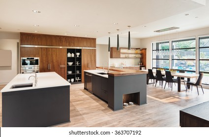 Beautiful Kitchen Interior with Two Islands,  Two Sinks, Cabinets, and Hardwood Floors in New Luxury Home
