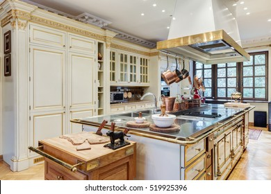 Beautiful Kitchen with Island and with copper utensils, Sink, Cabinets, and Hardwood Floors in New Luxury Home