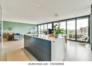 Beautiful kitchen island with plant and fresh fruit on it in a spacious room
