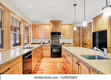 Beautiful kitchen with light wood cabinets, granite counter tops and black appliances.