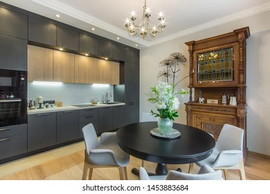 Beautiful kitchen in luxury contemporary apartment. Modern interior with round breakfast table and flowers