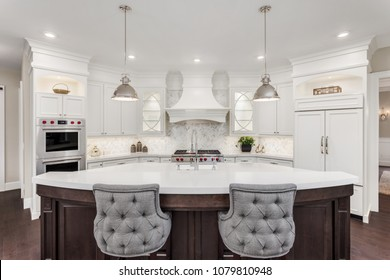 Beautiful Kitchen in Luxury Home with large island, refrigerator, pendant lights, double ovens, range, and hood.  Cabinets and Island are off-white.