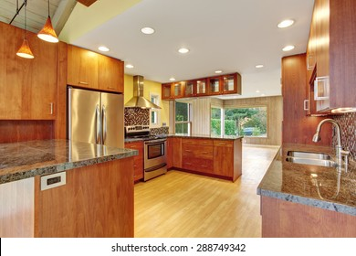 Beautiful kitchen with marble counters and hardwood floor. Cherry kitchen with open floor plan.