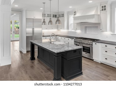 Beautiful Kitchen in New Luxury Home with Refrigerator, Oven, Hardwood Floors, Kitchen Island, and Pendant Lights