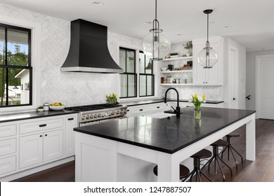 Beautiful Kitchen in New Luxury Home. Features Black Counters and Island, with White Woodwork and Cabinetry.