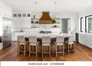 Beautiful Kitchen in New Luxury Home: White Cabinets Contrast Against Rich Hardwood Accents and Floor. Features Huge Kitchen Island