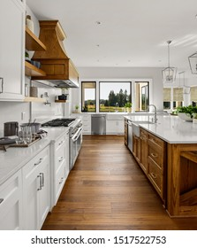 Beautiful kitchen in new luxury home with hardwood floors, two farmhouse sinks, and white cabinets.