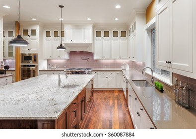 Beautiful Kitchen in New Luxury Home, with Wrap Around Cabinets, Hardwood Floors, Pendant Lights, and Large Granite Island