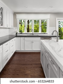 Beautiful Kitchen in New Luxury Home with Hardwood Floors, Two Sinks, White Cabinets, and Gorgeous View of Lush Foliage