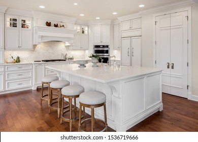 Beautiful kitchen in new traditional style luxury home. Features white island, counters, and cabinetry, and dark hardwood floors