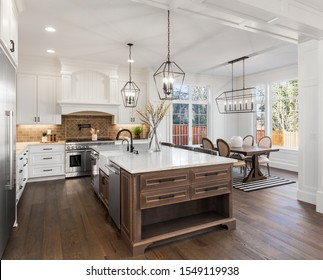Beautiful kitchen in new traditional style luxury home, with quartz counters, hardwood floors, and stainless steel appliances. Lights are on. - Shutterstock ID 1549119938