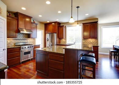 Beautiful kitchen room with oak cabinets, steel appliances. View bar counter with black chairs.