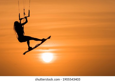 beautiful kitesurfing woman silhouette kiteboarder jumping sport at sunset golden hour, kite surfing girl kiteboarding jump
