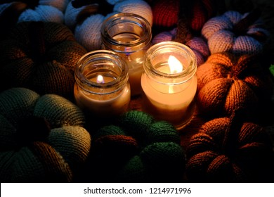 Beautiful knitted pumpkin from yarn with three candles in night, candle light make colorful background, nice handmade product from leisure activities