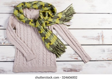 Beautiful knitted sweater and green scarf on a wooden background. Warm bright winter set.