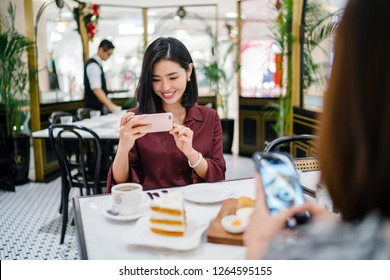 A beautiful Korean Asian woman is taking a photograph of hear food before having tea and cake with a friend in a trendy cafe.