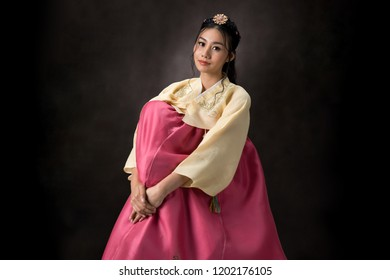 Beautiful Korean girl in Hanbok dress. Looks adorable and elegant. standing front of black background.