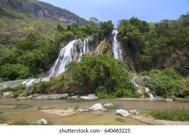 Beautiful La Conchuda waterfall surrounded by lush green vegetation with high canyon walls in background in Rio la Venta Canyon in Chiapas, Mexico on clear sunny day