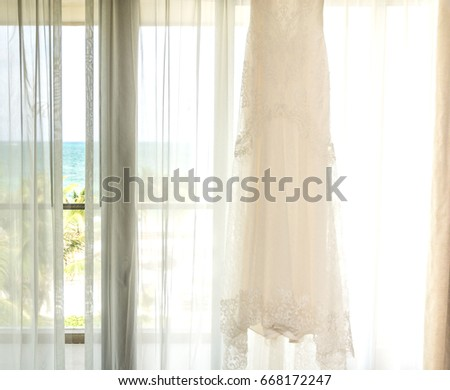 d4a7af451f9 A beautiful lace wedding dress hangs in a window illuminated by sunlight  overlooking a beach in