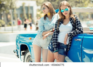 Beautiful ladies in sun glasses posing near vintage car cabriolet