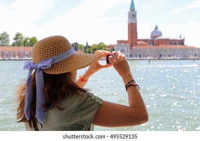 beautiful lady with a big straw hat taking a picture in the basin of San Marco in Venice in Italy