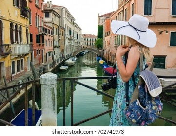 beautiful lady with a big straw hat taking a picture in Venice in Italy