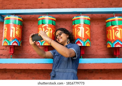 a beautiful lady in a blue dress taking selfie with a smart phone in front of buddhist prayer wheels in a monastery in Sikkim in India