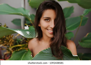 Beautiful lady with curly hair and green eyes smiles sweetly. Woman with long eyelashes posing against backdrop of tropical plant